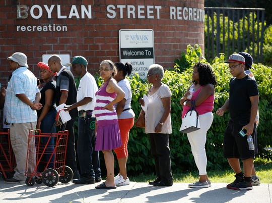 City residents line up at the Boylan Street Recreation Center with cases of bottled water, Monday, Aug. 12, 2019, in Newark, N.J., after recent U.S. Environmental Protection Agency tests showed elevated levels of lead in the drinking water in some areas of Newark, despite filters that had been distributed earlier.