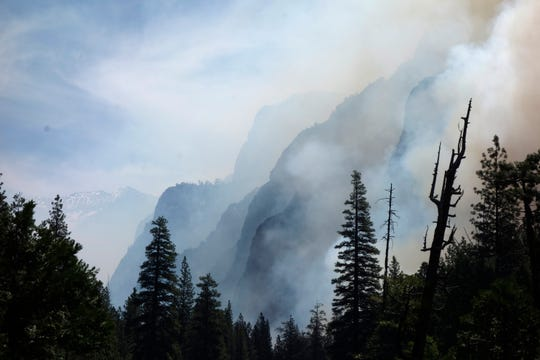 In this June 11, 2019 photo, canyon walls are shrouded with smoke from a prescribed burn in Kings Canyon National Park, Calif.