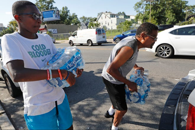 Volunteer Matthew Tiggs, left, helps Newark resident Mack Mayton load cases of bottled water into the trunk of his car, Monday, Aug. 12, 2019, in Newark, N.J., after Mayton picked it up at the Boylan Street Recreation Center.