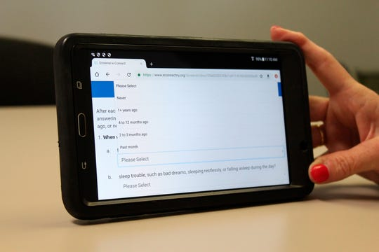 An Albany County probation official on Monday, Aug. 5, 2019, holds up a tablet used to conduct the e-Connect program, at the Albany County Probation Department office.