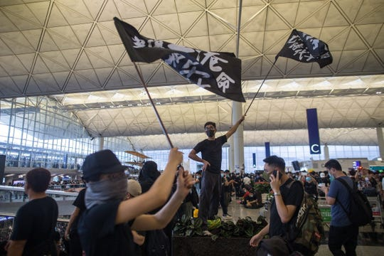Protesters wave flags as they occupy Hong Kong Chek Lap Kok International Airport in Hong Kong on Aug. 12, 2019. Hong Kong has been gripped for weeks by mass protests, which began in June 2019 over a now-suspended extradition bill to China and have developed into an anti-government movement.