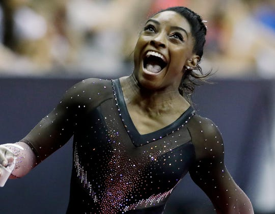 Simone Biles celebrates after competing in the uneven bars to win the all around senior women's competition at the 2019 U.S. Gymnastics Championships.
