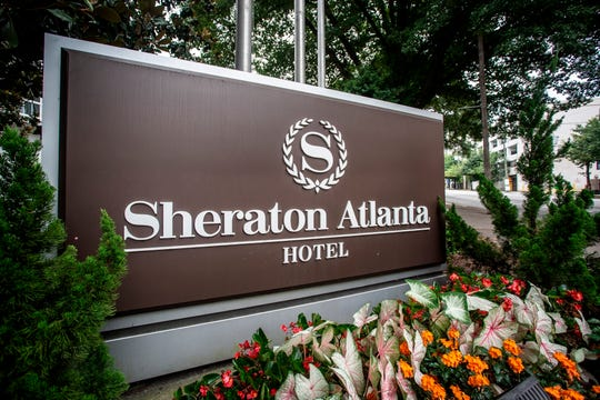 "In this Wednesday, July 31, 2019 file photo, the sign at the entrance to the Sheraton Atlanta Hotel is seen, in Atlanta. A lawsuit alleges ""negligence in the operation and maintenance of the water systems"" caused a Legionnaires' disease outbreak at a downtown Atlanta hotel."