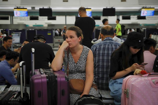 Australian Penny Tilley, center, reacts next to stranded travelers at the closed check-in counters at the Hong Kong International Airport.