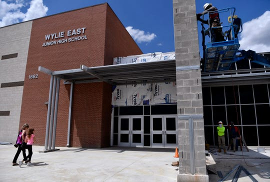 Students and families enter Wylie East Junior High School Tuesday for campus tours as workmen continue to finish the school facade August 13, 2019.