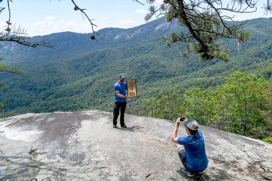 """Peter Barr, trails coordinator for the Hendersonville-based Conserving Carolina land trust, holds an award from the national Coalition for Recreational Trails while standing on Grey Rock along the Weed Patch Mountain Trail July 25, 2019. In June in a ceremony on Capitol Hill, Barr, for his sustainable design work, Chris """"Shrimper"""" Khare, of Terra Incognita Trail Specialists, who led the construction, and Conserving Carolina received the award in the category of trail design and construction."""