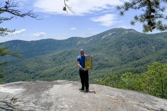 Peter Barr, trails coordinator for the Hendersonville-based Conserving Carolina land trust, holds an award from the national Coalition for Recreational Trails while standing on Grey Rock along the Weed Patch Mountain Trail July 25, 2019.