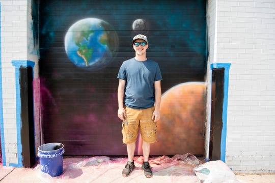 Taylor Ladd from Battle Creek poses for a portrait as he makes progress on his mural for Color the Creek on Tuesday, Aug. 13, 2019 in Battle Creek, Mich. Taylor's mural can be found on the back of 50 W. Michigan Ave.
