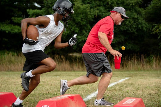 Marshall senior Thailan Taylor runs drills with coach Shaun Lowridge during their first practice of the season on Monday, Aug. 12, 2019 at Marshall High School in Marshall, Mich.