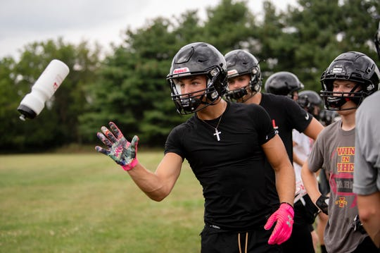 Marshall junior Ezra McAllister catches a water bottle during the first football practice of the season on Monday, Aug. 12, 2019 at Marshall High School in Marshall, Mich.