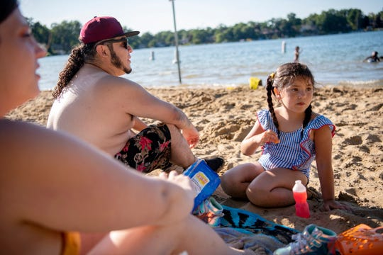 Khali Peredia, 5, shares snacks with her parents Miguel Peredia and Alexandra Zylman on Willard Beach Park of Goguac Lake on Friday, Aug. 9, 2019 in Battle Creek, Mich.