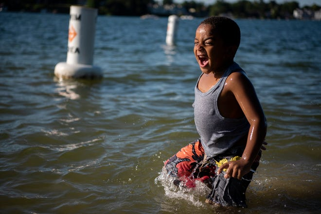 Verse Burnett, 7, splashes in the water of Goguac Lake on Friday, Aug. 9, 2019 in Battle Creek, Mich.
