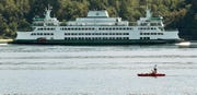 A kayaker paddles past Bachmann Park as the Washington State Ferry Chimacum heads for the Bremerton Ferry Dock on Tuesday, August 13, 2019.