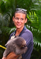 Curator of Animals Lauren Hinson holding a two toed sloth named Lorenzo that she has raised.