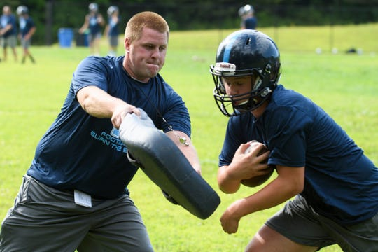 Head coach Nick Michaud participates in a running back drill during the Mount Mansfield Cougars football practice at MMU High School on Tuesday afternoon August 13, 2019 in Jericho, Vermont.