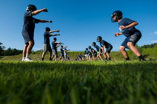 Players participate in tackling drills during the Mount Mansfield Cougars football practice at MMU High School on Tuesday afternoon August 13, 2019 in Jericho, Vermont.