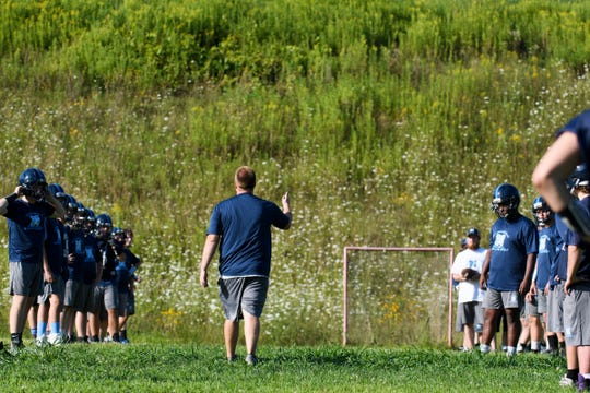 MMU head coach Nick Michaud talks to the players during the Mount Mansfield Cougars football practice at MMU High School on Tuesday afternoon August 13, 2019 in Jericho, Vermont.