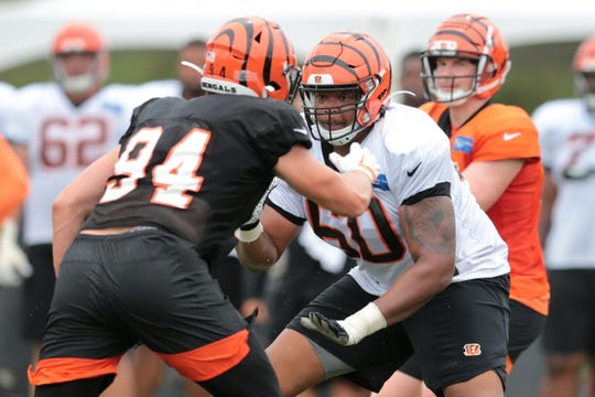 Cincinnati Bengals offensive guard Mike Jordan (60) blocks Cincinnati Bengals defensive end Sam Hubbard (94) as Cincinnati Bengals quarterback Andy Dalton (14) takes the snap during Cincinnati Bengals training camp practice, Tuesday, Aug. 13, 2019, at the practice fields next to Paul Brown Stadium in Cincinnati.