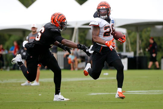 Cincinnati Bengals running back Joe Mixon (28) carries the ball as Cincinnati Bengals defensive end Carlos Dunlap (96) defends during Cincinnati Bengals training camp practice, Tuesday, Aug. 13, 2019, at the practice fields next to Paul Brown Stadium in Cincinnati.