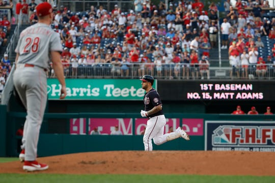 Washington Nationals' Matt Adams, back center, rounds the bases for his two-run home run as Cincinnati Reds starting pitcher Anthony DeSclafani (28) walks back to the mound during the first inning of a baseball game at Nationals Park, Monday, Aug. 12, 2019, in Washington.