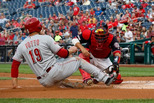 Cincinnati Reds' Joey Votto (19) is out at the plate on a tag by Washington Nationals catcher Kurt Suzuki, right, during the first inning of a baseball game at Nationals Park, Monday, Aug. 12, 2019, in Washington.
