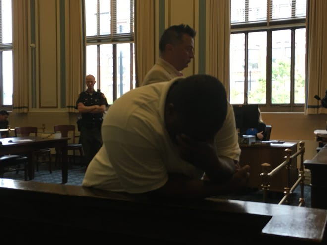 Ronald Williams, his face in his hands, leans against the jury box in Hamilton County Common Pleas Judge Patrick Foley's courtroom, as the mother of the man who died in a crash Williams caused talks about her son.