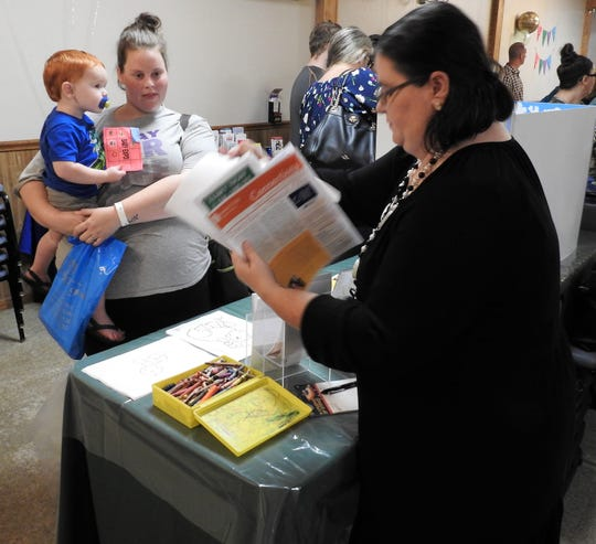 Kaitlyn Murray with her son, Corben, receives information on Coshocton Public Library programming from Amanda Gress, youth services assistant, at the recent Baby Expo at the Coshocton Moose Lodge.