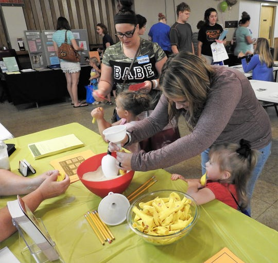 Brittany Reed and her daughter, Lilly Reed, 4, and Nakita Fisher and her daughter Journee Fisher, 2, work on a craft of filling a balloon with sand at the recent Baby Expo at the Coshocton Moose Lodge.