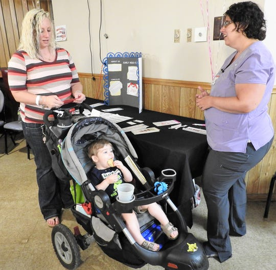 Erin Porter with her son Mason Donley talks with Katy Martin of Early Head Start at the recent Baby Expo at the Coshocton Moose Lodge. More than 70 attended the event for expectant and new mothers.