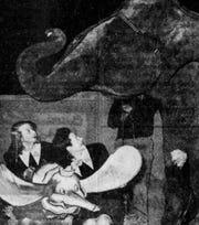 """Dumbo, or at least a reasonably accurate facsimile of the Disney character, in 1941 pays a Christmas visit to Baby Mine, the elephant owned by Iowa's schoolchildren. Two ticket girls from the Orpheum Theater, Gretchen Staads, left, and Grace Spayde, went to visit Mine elephant at his home at the Iowa State Fairgrounds. """"Dumbo"""" was the movie was playing at the Orpheum."""