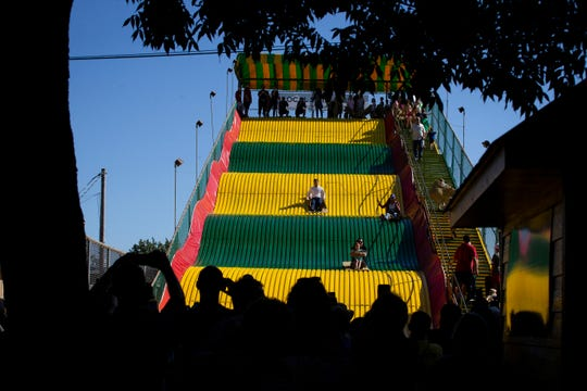 South Bend Indiana Mayor and 2020 Democratic presidential candidate Pete Buttigieg, center, rides the Giant Slide with Harris Mayer, 4, of Iowa City, bottom, during the Iowa State Fair on Tuesday, Aug. 13, 2019 in Des Moines.