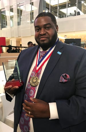 Michael Smith, a volunteer pitchman for Comcast's low-cost Internet program, was recognized by his company for his efforts.