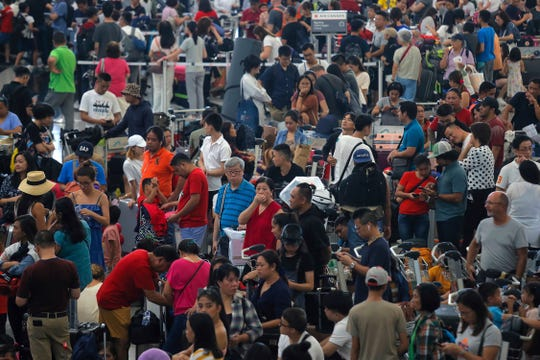 Stranded travellers gather at the departure hall of the Airport in Hong Kong, Tuesday, Aug. 13, 2019.