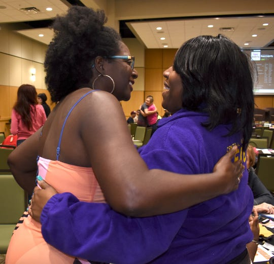 """Positive S.I.S.T.E.R.S. Founder Kimle Nailer of Detroit, left, hugs SEIU Local 517M President Joey Combs of Novi at a """"Superlocal x Detroit"""" event at Wayne State  on Aug. 10."""