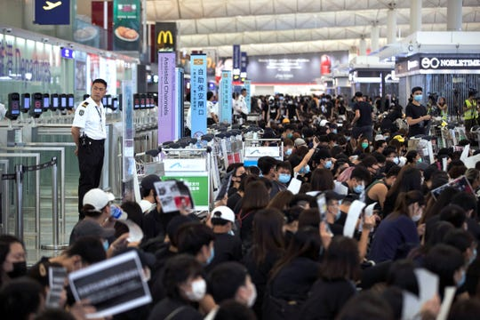 Airport security personnel look on as protesters using luggage trolleys to block the departure gates during a demonstration at the Airport in Hong Kong, Tuesday, Aug. 13, 2019.
