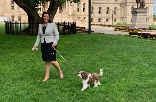 Michigan's first pooch, Kevin, strolls with Gov. Gretchen Whitmer on the grounds of the state Capitol.