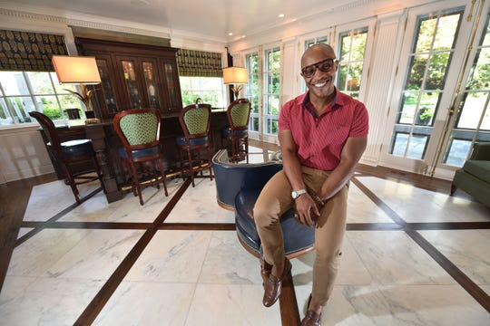Corey Damon Jenkins, 42, sits in the home he decorated for a Birmingham client. He recently opened a second office in New York. Ten years after losing his job in the automotive industry and being forced to rely on unemployment, he says he's so grateful for all the opportunities that have come along in his design career.