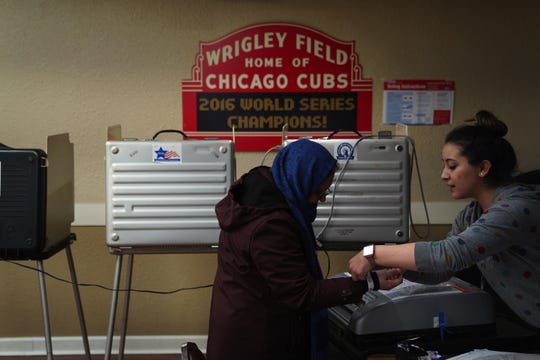"An election coordinator puts an ""I voted"" wristband on a voter in the spring in Chicago."