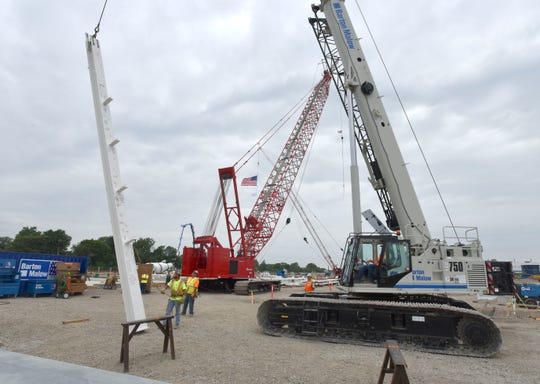 Construction workers set the first vertical column for the new paint shop at the FCA Mack Avenue construction location on Aug. 13.