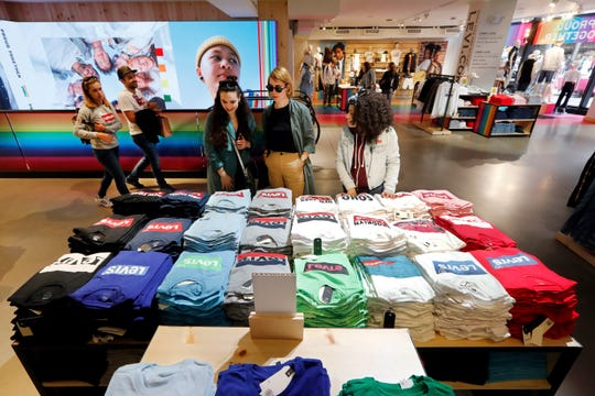 A pair of shoppers, center, in the Levi's store in New York's Times Square, survey a T-shirt display.