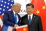 "In this  June 29, 2019, file photo, U.S. President Donald Trump, left, shakes hands with Chinese President Xi Jinping during a meeting on the sidelines of the G-20 summit in Osaka, western Japan. Trump decried on Twitter, Tuesday, what he called China's ""massive"" intervention to suppress the yuan, portraying the U.S. as the beneficiary of his tariffs on Chinese imports and suggesting – despite recent evidence to the contrary – that prices aren't rising."