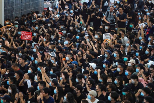 Protesters gesture as they stage a sit-in rally at the Airport in Hong Kong, Tuesday, Aug. 13, 2019.