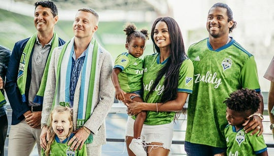 Russell Wilson, right, and wife Ciara, join Macklemore and other members of the Major League Soccer Seattle Sounders ownership group.