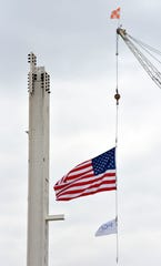 The American flag and FCA flag blow in the breeze after workers set the first vertical column for the new paint shop at the FCA Mack Avenue construction site.