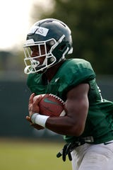 Michigan State running back Elijah Collins runs during a drill.