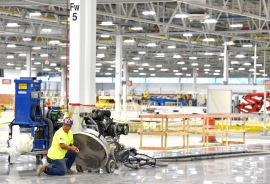 A worker prepares to polish the floor in Fiat Chrysler's new body shop.