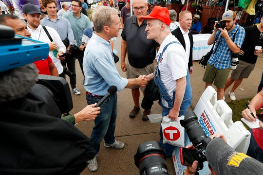 Democratic presidential candidate and businessman Tom Steyer, left, talks with a fairgoer before speaking at the Des Moines Register Soapbox during a visit to the Iowa State Fair, Sunday, Aug. 11, 2019, in Des Moines, Iowa.  Steyer said Tuesday he's met one of the thresholds to make the party's next debate in September.