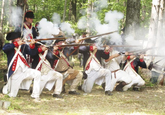Re-enactors fire their muskets during a Revolutionary War battle re-creation at Newtown Battlefield State Park.