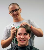 Riley Haynes, 14, shaves the head of his best friend since first grade, Sam Alldredge, 14, at North High School's Bondurant Stadium Monday evening. It was Alldredge's idea for their football teammates to have their heads shaved after Haynes' cancer treatment caused his hair to fall out.