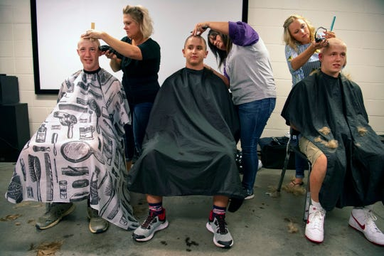 "Riley Haynes, 14, center, and teammates Cale Johnson, 15, left, and Tyler Gilman, right, are the first to have their heads shorn at North High School's Bondurant Stadium Monday evening. ""Well, I'm gonna get my potato baked tomorrow,"" Gilman, 17, a senior linebacker at North said as he rubbed the stubble on his freshly shaven head."